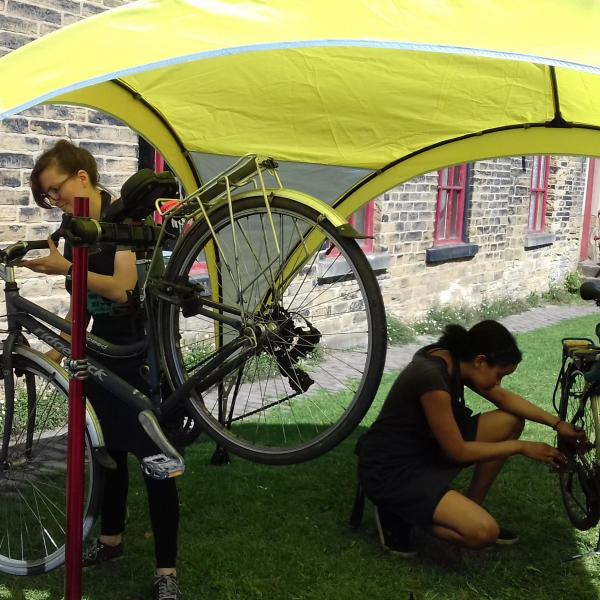 Two people fixing bikes under a yellow shelter on a grassy space outside a stone building.