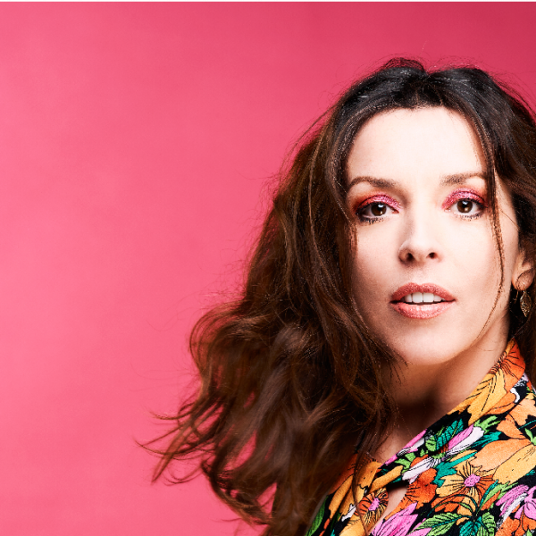 Comedian Bridget Christie wearing colourful clothes against a pink backdrop