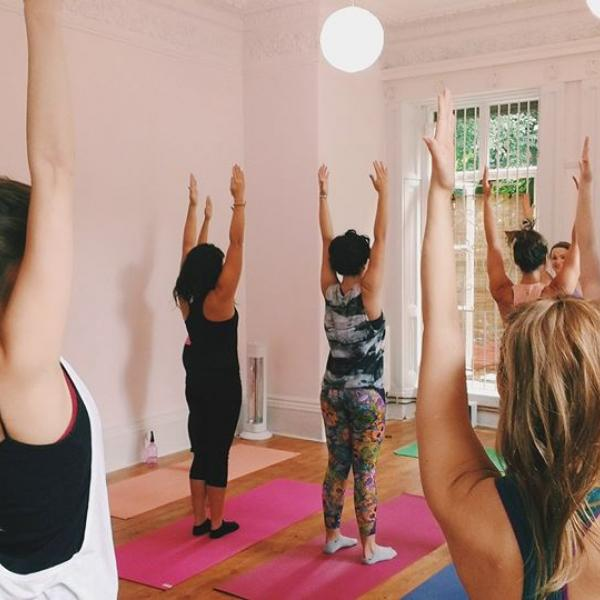Image of students during their class in a sun salutation.