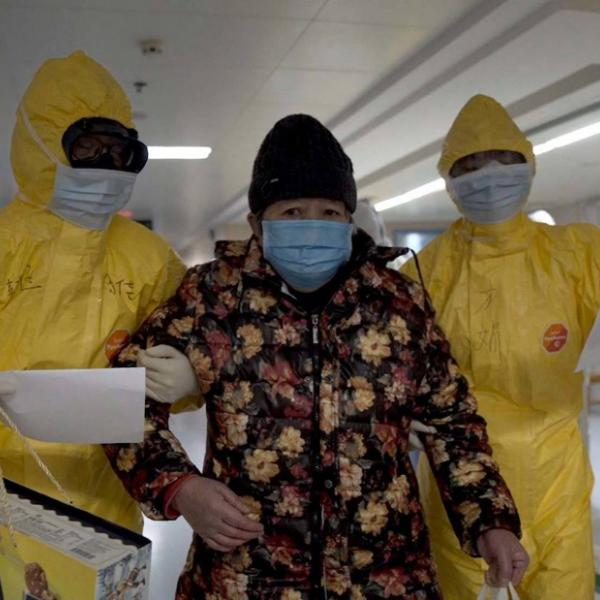 A woman in a mask is being led by two doctors in PPE