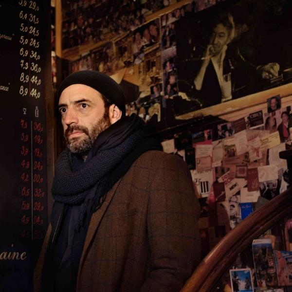 Adrian Crowley dressed in winter coat stood on a dimly lit stairs at a quirky restaurant