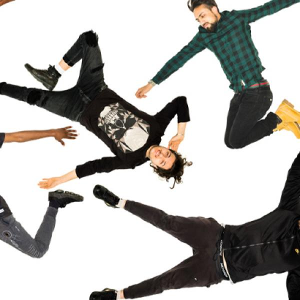 Six performers, viewed from above, jumping, arms outstretched