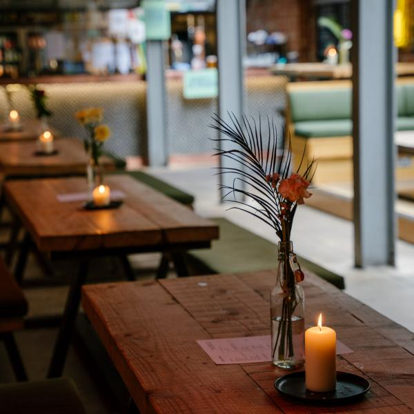 Image of bar with flowers and candles on tables.