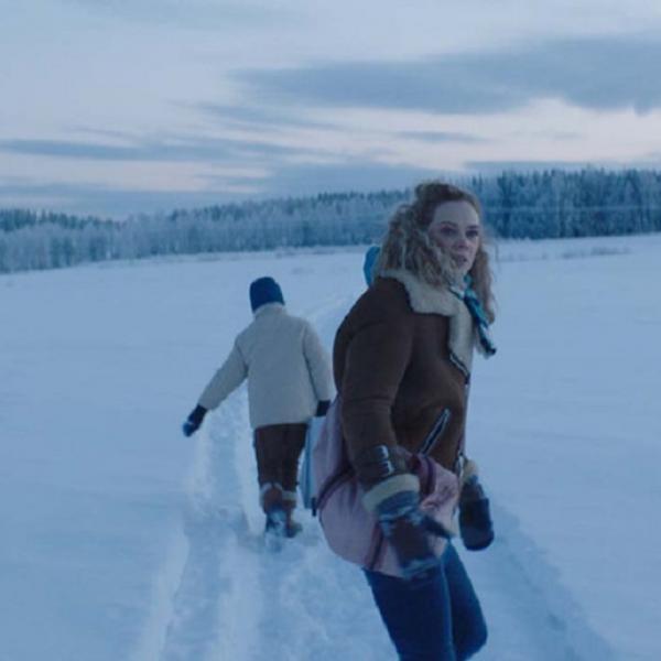 two people walking through snow