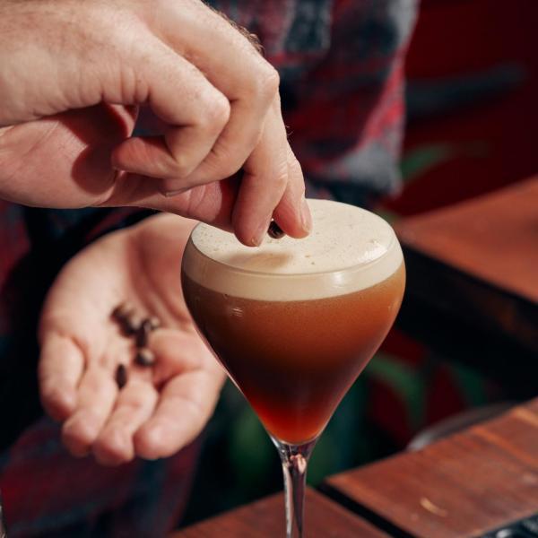 A Liquor Studio Mixologist placing coffee beans onto an Espresso Martini