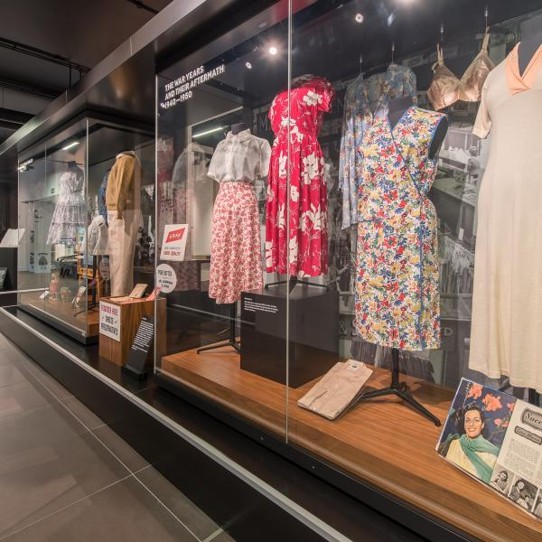 The image shows a glass display cabinet containing vintage 1940s women's clothing including a floral apron and silk bra