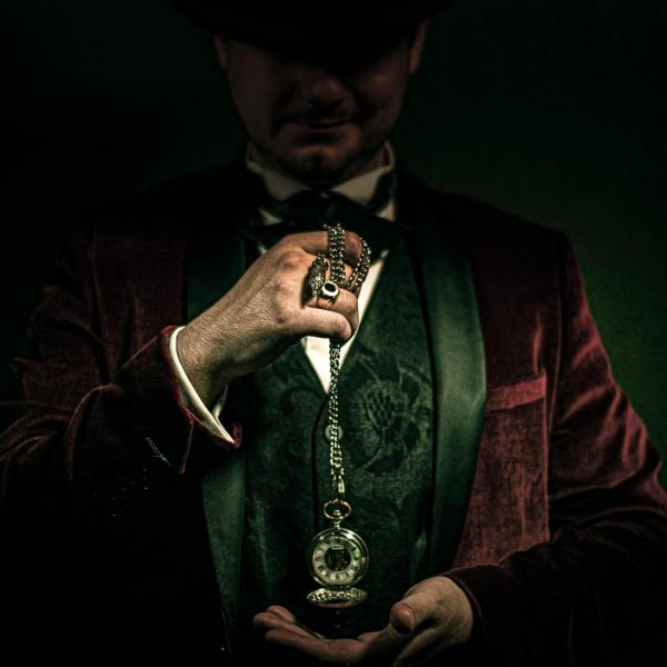 A man in shadows, dressed in a velvet coat and holding a pocket watch.