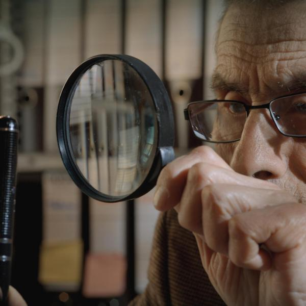 An old man looks at a pen through a magnifying glass