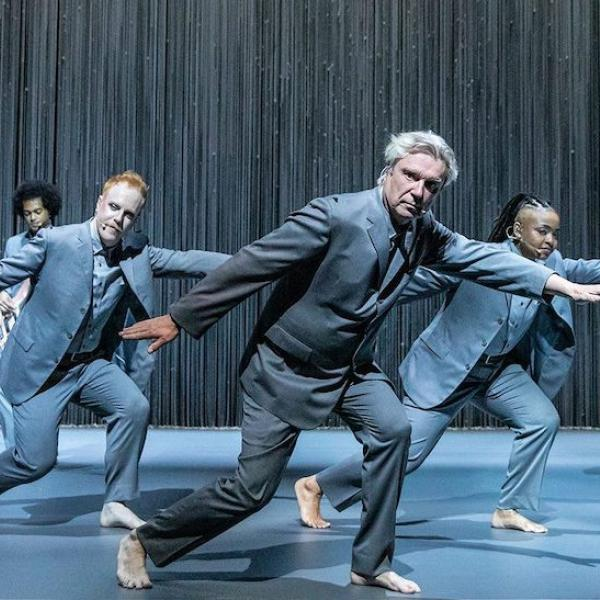 A group of people dressed in grey suits dance and play music on a stage