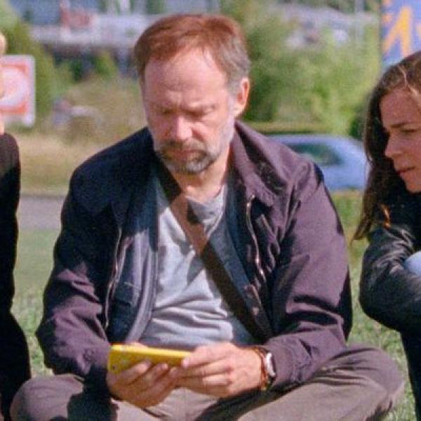 Three friends gather round a smartphone.
