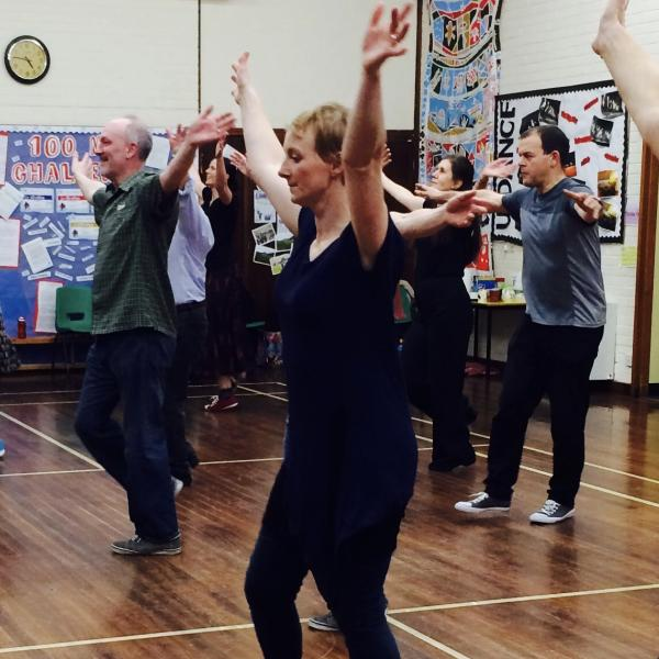 Group of people of all ages and abilities learning dance steps