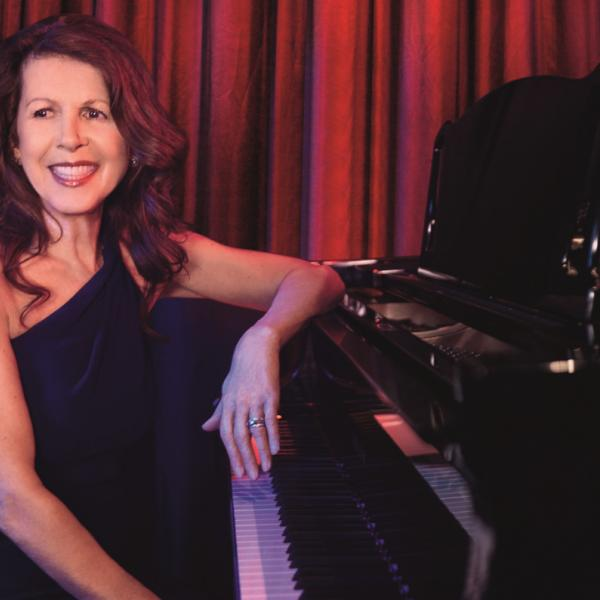 Musician Elkie Brooks sat at a grand piano