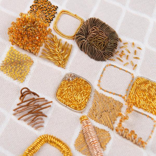 Image of a range of intricate goldwork embroidered patches using different gold threads on a cream checked cotton background