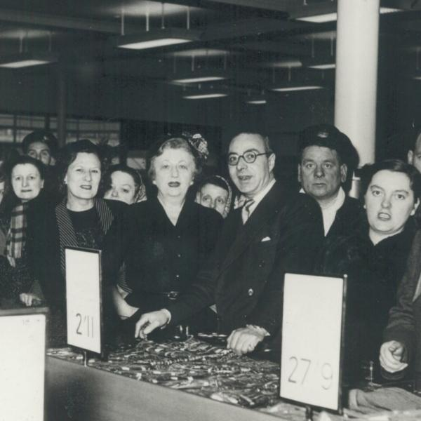 Black & white photograph showing Flora Solomon in the centre surrounded by customers inside an M&S store in the 1950s.
