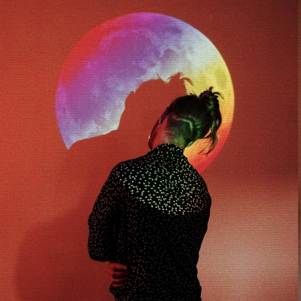 Fwar, head tilted, facing a wall with rainbow-coloured projection of Moon