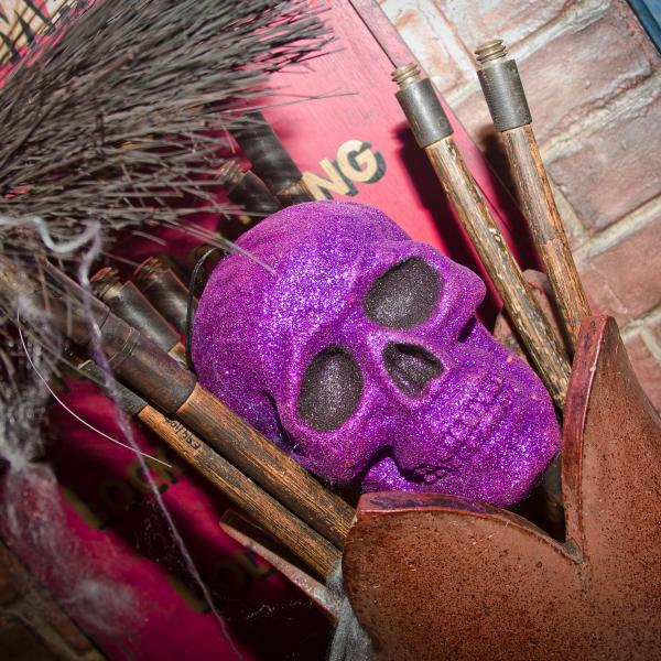 A glittery pink skull sits in a Victorian chimney pot hung with cobwebs.