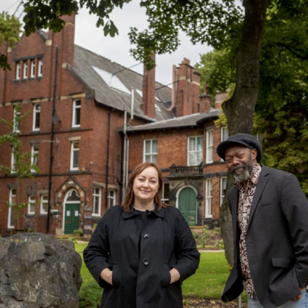 two people standing infront of a Victorian red brick building