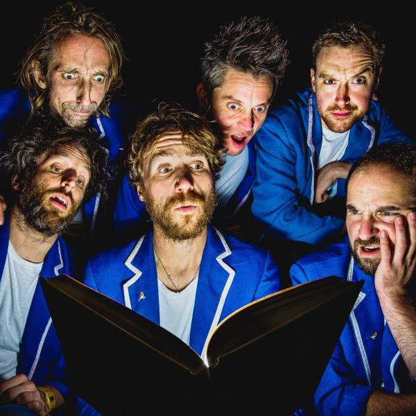 Six men in blue pyjamas looking at an open book illuminating their faces