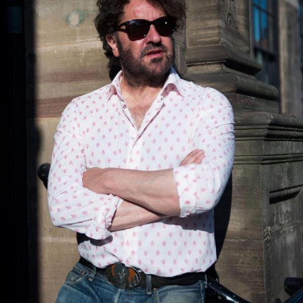 Ian Prowse in jeans and a shirt and sunglasses