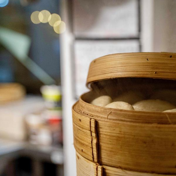 Bamboo steamer, slightly open showing fluffy bao buns inside.
