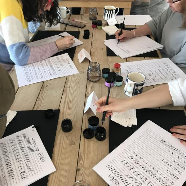 Image of people sitting at a table practicing calligraphy with pots of different coloured inks, calligraphy pens and practice sheets.