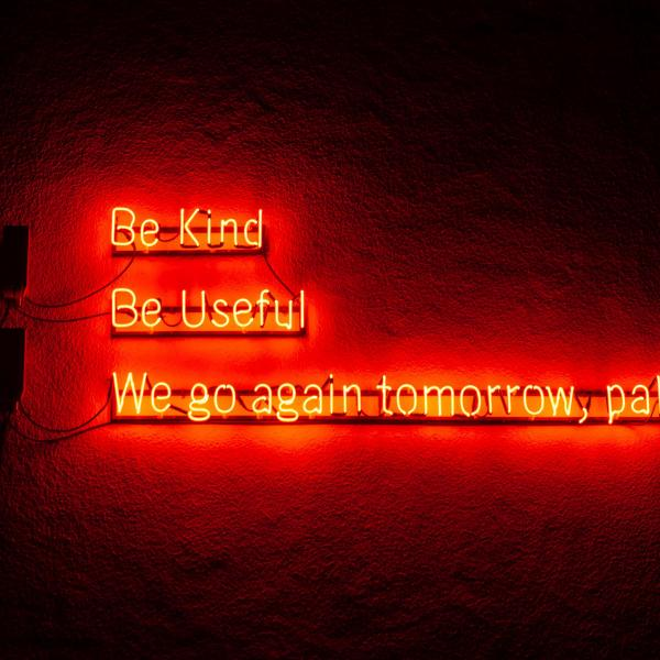 A neon light saying Be Kind, Be Useful, We go again tomorrow, pals