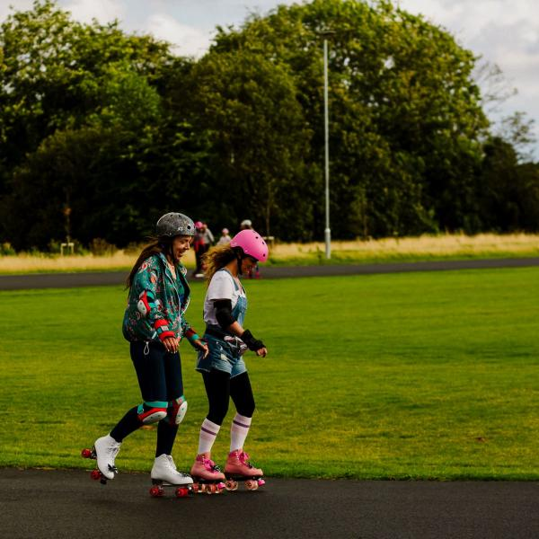Two roller skaters with helmets and protective pads on are skating on a tarmac path near grass.