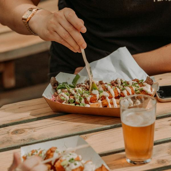 Two people tuck into portions of street food on a wooden table with a pint of beer
