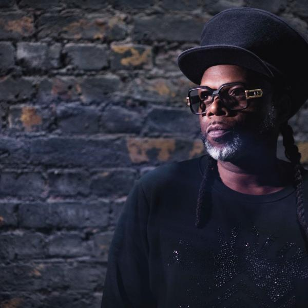 Musician Jazzie B wearing shades and a hat.
