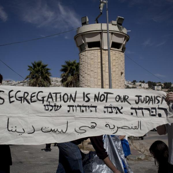 two people standing in front of a control tower and holding a banner saying Segregation is not our Judaism.