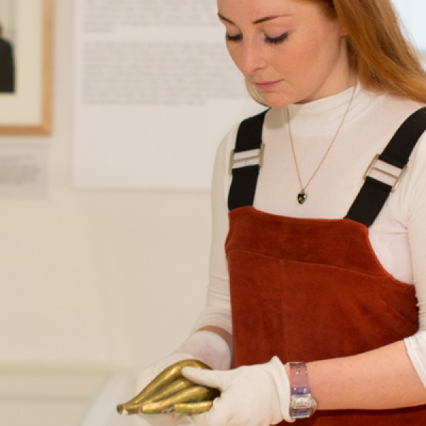A member of staff putting objects on display in the Gallery.