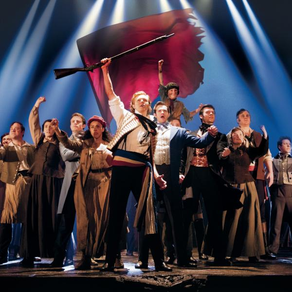 The cast of Les Miserables, marching, holding a gun aloft and waving a red flag
