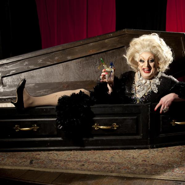 a woman finely dressed with a cocktail climbing out of a coffin laughing