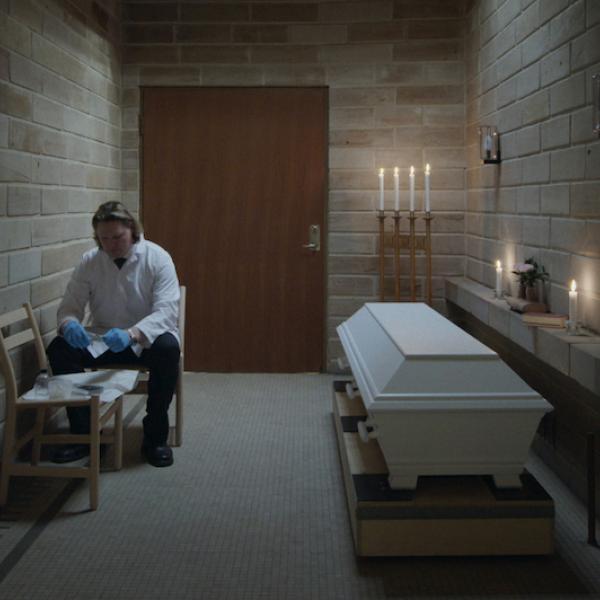 A man cleans utensils next to a casket