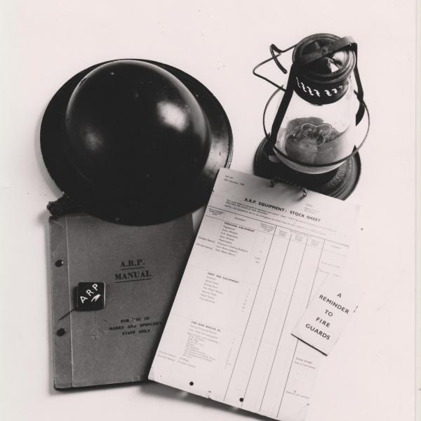 Image shows items relating to ARP (Air Raid Precautions) including manual, badge and lantern.