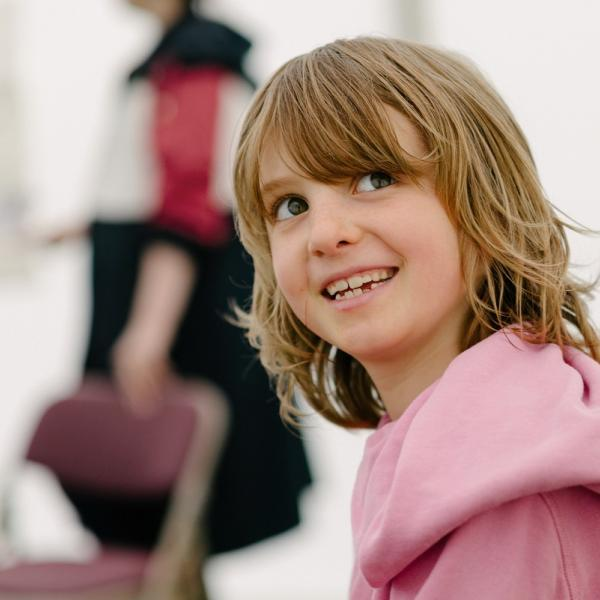 A child in a pink hoodie smiles towards the camera