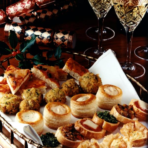 Image shows a tray full of finger foods with two glasses of cava and christmas crackers in the background.