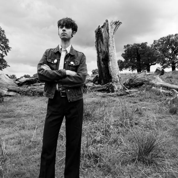 Black and white photo of Phil Madeley stood arms crossed in a field in front of a tree stump