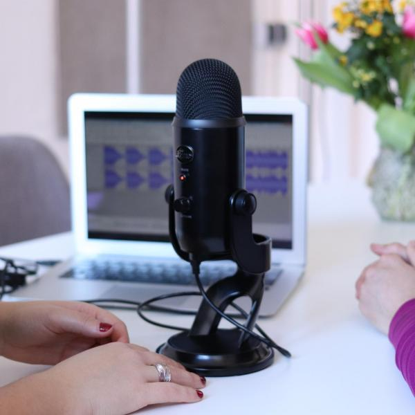 Two people sitting at a table with a podcast microphone and laptop, flowers in background
