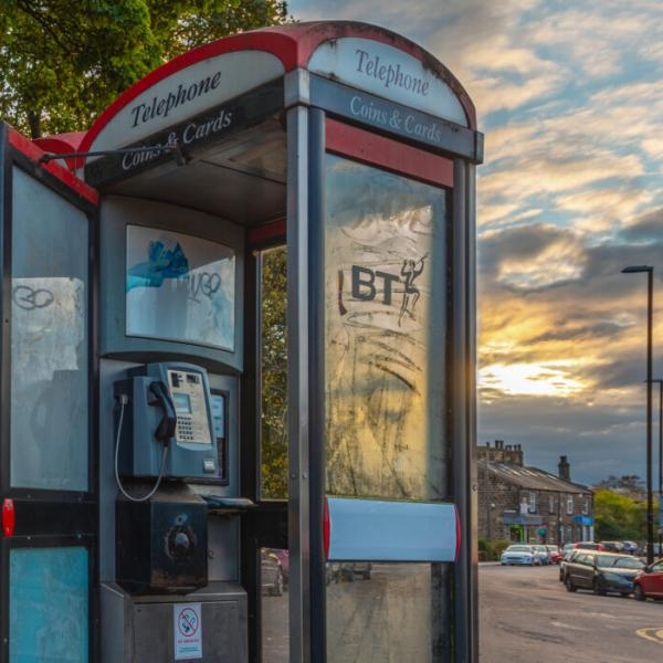 A Leeds phone box in front of a sunset sky. You can see the golden sun through the window.