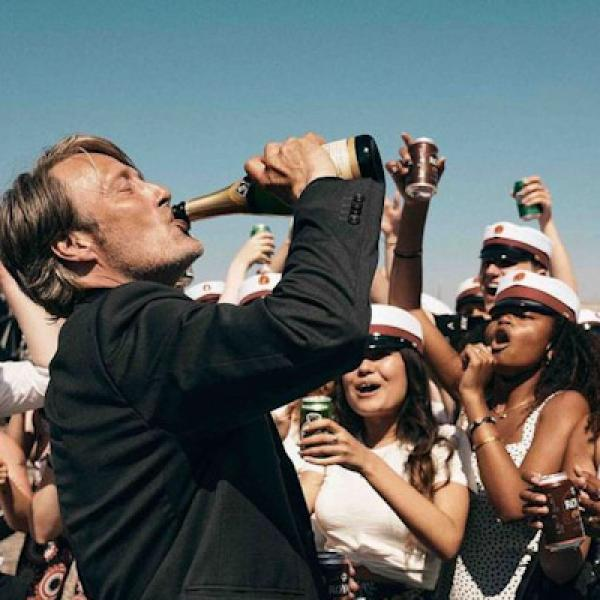 Man is drinking a bottle of champagne surrounded by a crowd