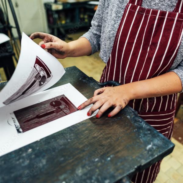 Person in apron lino printing.