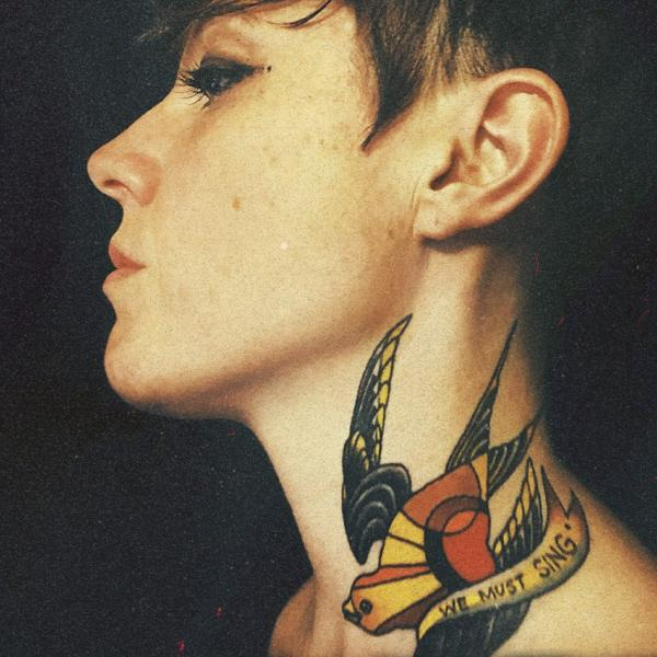 Photo of a woman's profile with swallow tattoo on her neck