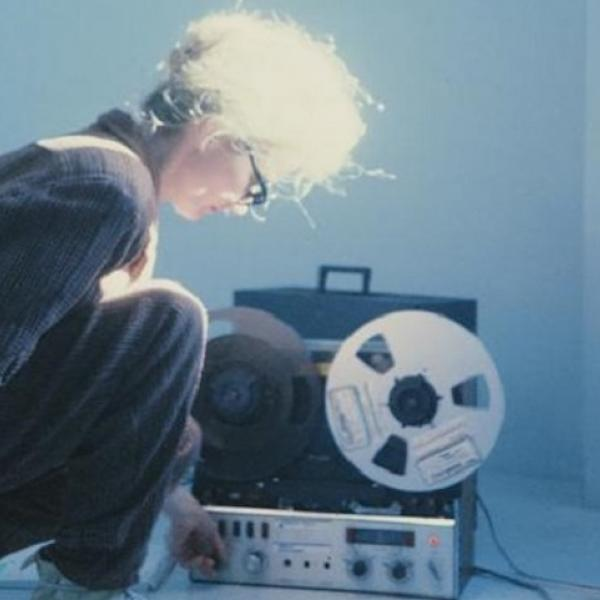 A woman kneels by some music equipment