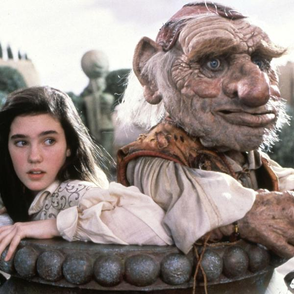 Image shows a young woman and a large magical troll standing together in a large pot.