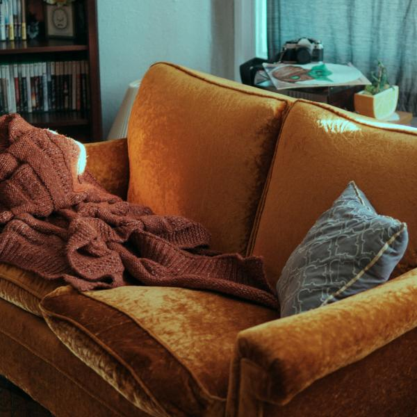 Picture of sofa with blanket and pillow on to show someone has been sleeping on it.