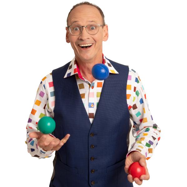Comedian Steve Royle, wearing a colourful shirt and waistcoat, juggling balls.
