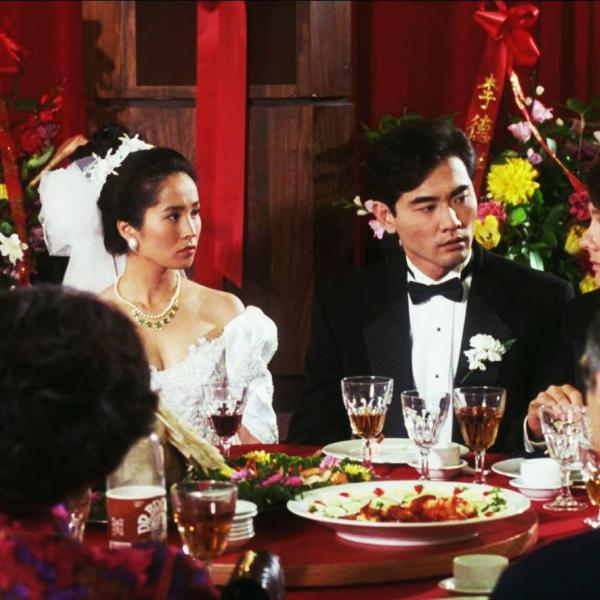 a group of people with bride and groom at a dining table with food and drink