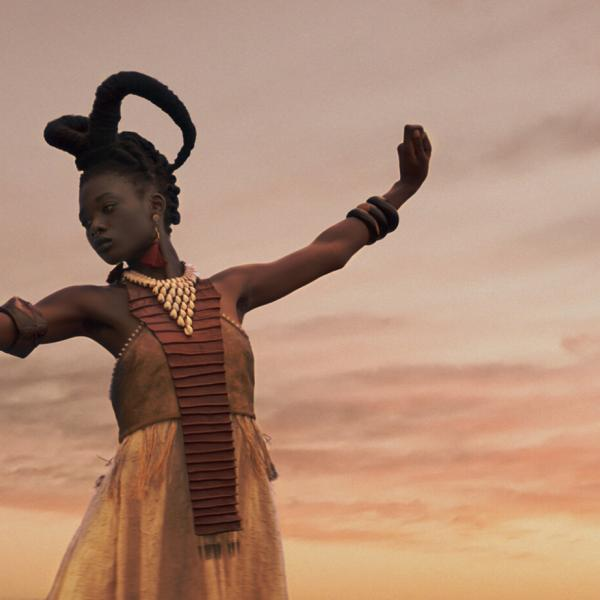 African woman stands with arms outstretched.