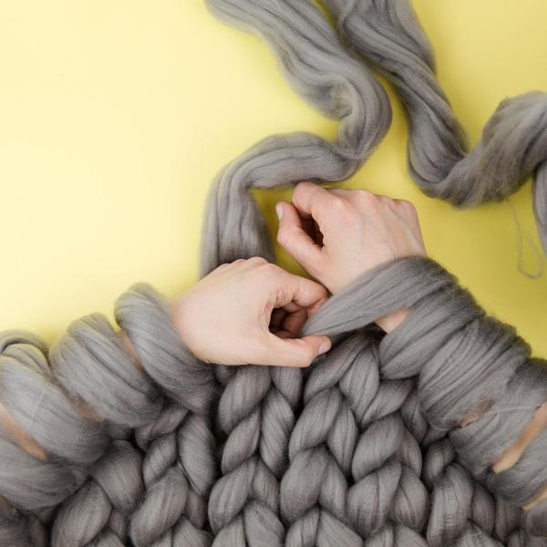 Image of arms knitting a throw using grey giant yarn on a yellow background
